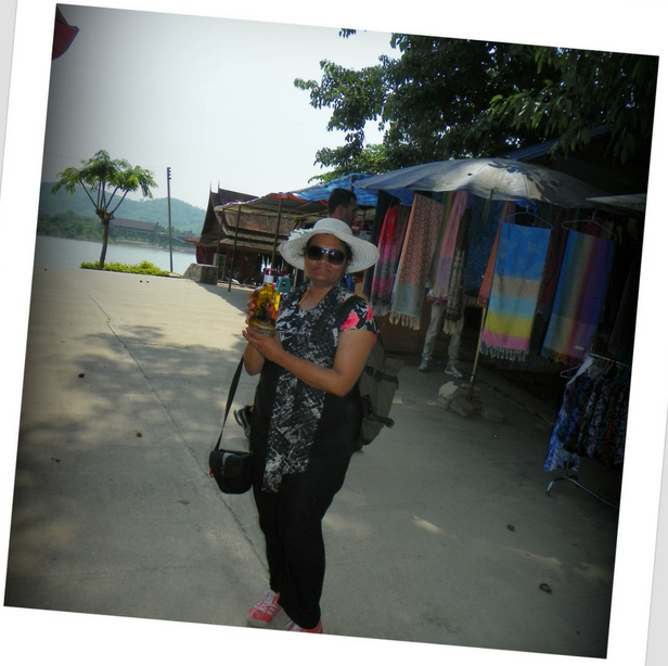 Me holding a snake wine bottle in Laos