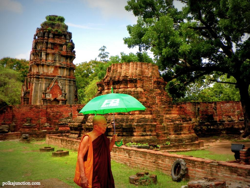 A monk with an umbrella exploring the Ayutthaya temples and ruins
